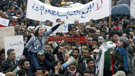 """People chant slogans during a protest in Casablanca February 20, 2011. Thousands of protesters took to the streets in Morocco on Sunday demanding King Mohammed give up some of his powers, dismiss the government and clamp down on corruption. The banner  reads: """"No to get money and power at the same time"""".  REUTERS/Macao (MOROCCO - Tags: POLITICS CIVIL UNREST IMAGES OF THE DAY)"""