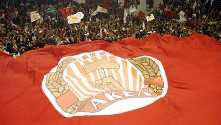 Cypriot supporters of communist party leader Demetris Christofias wave their national flag (white and yellow) next a huge AKEL party flag after announcing the official results of the east Mediterranean island's presidential elections.