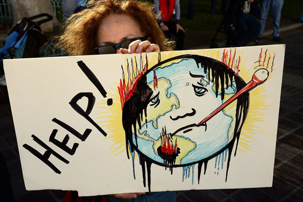 epa05048194 A woman holds a poster of a sick Earth as she joined hundreds of demonstrators who gathered in front of City Hall in Los Angeles, California, USA, 29 November 2015, on the eve of the COP21 Climate Conference in Paris, France, where global climate change issues will be discussed.  Worldwide demonstrations were held to push for changes in governmental policies to address climate change.  EPA/MIKE NELSON